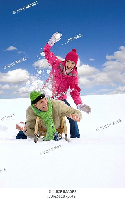 Woman throwing snowball at boyfriend laying on sled