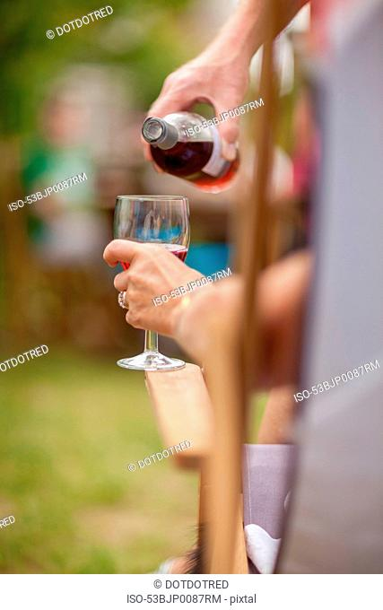 Woman pouring glass of wine outdoors