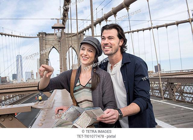 Happy couple with map on Brooklyn Bridge