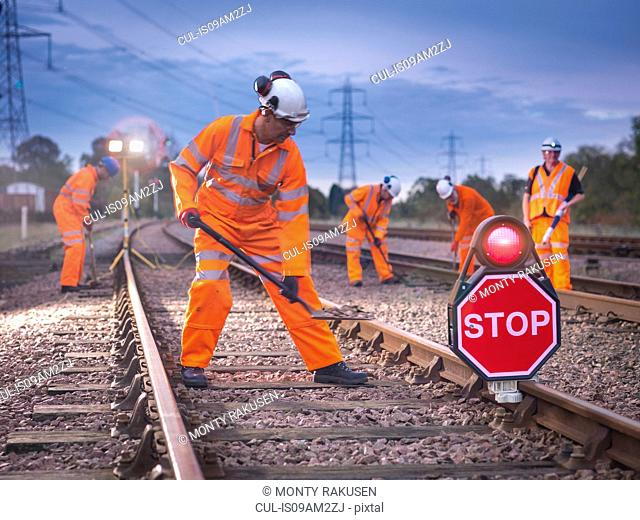 Railway maintenance workers on track with stop sign at night