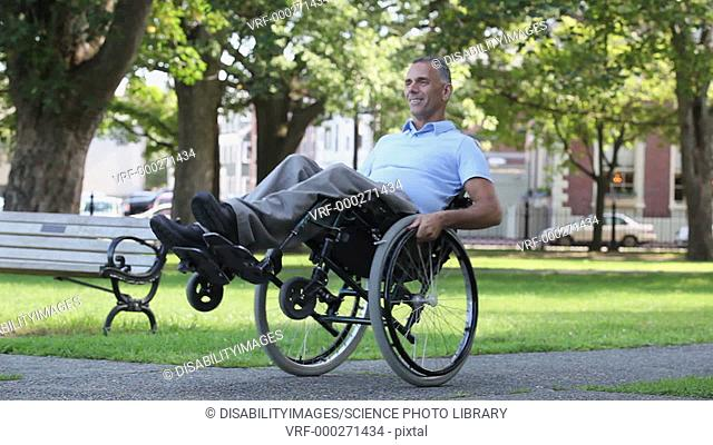 MODEL RELEASED. Man with a spinal cord injury in a wheelchair doing tricks in his chair in a park