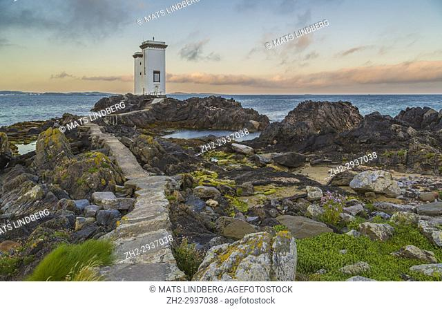 Port Ellen Lighthouse, Carraig Fhada Lighthouse in evening light after sunset with nice colors on the skye with cliffs and seaweed in foreground, Port Ellen