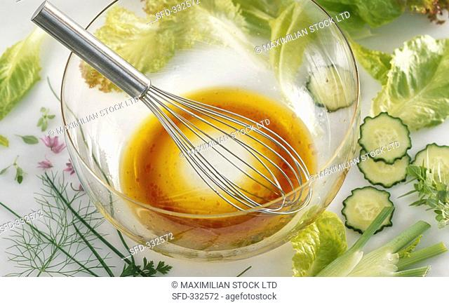 Red wine vinegar and olive oil dressing in glass bowl, salad ingredients