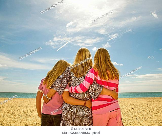 Mother and daughters hugging on beach