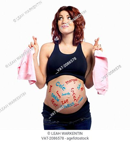Portrait of a pregnant woman with baby names written all over her belly holding pink clothes with her finger's crossed, edmonton alberta canada
