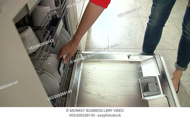 Woman pulls rack from dishwasher and starts to unload plates. Shot on Sony FS700 in PAL format at a frame rate of 25fps