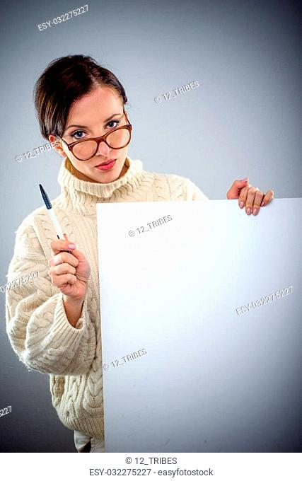 Scholarly attractive serious young woman holding a blank white sign as she peers over her glasses at the camera with a pen in her hand