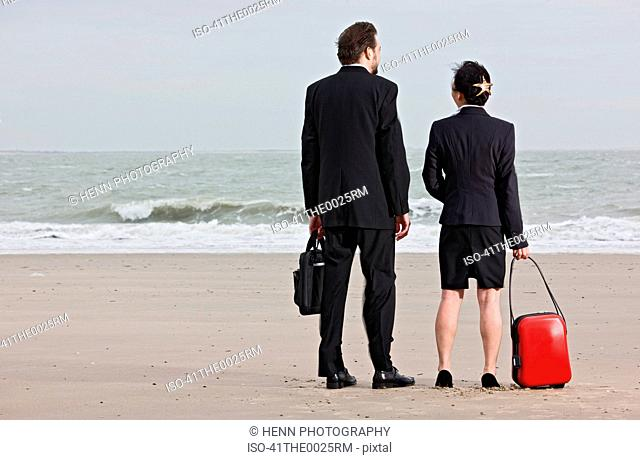 Businesspeople with luggage on beach