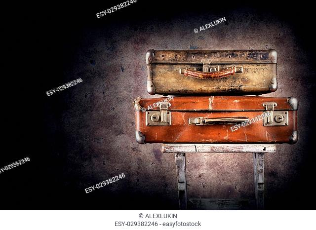Vintage suitcases on chair on grange background