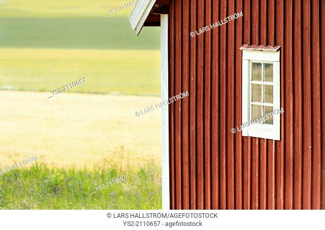 Small red wooden cottage with window overlooking field, Sweden