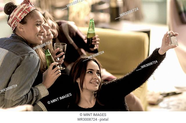 Four young women sitting on a sofa, laughing, taking a selfie, holding beer bottles