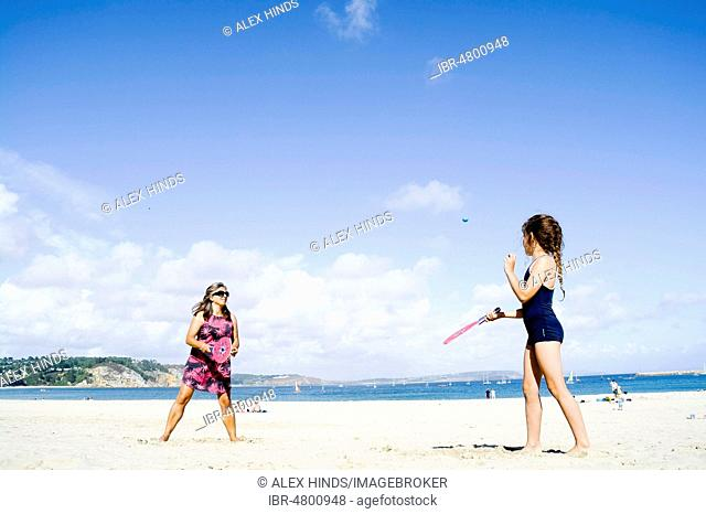 Mother and daughter playing beach bat and ball, Morgat, Brittany, France