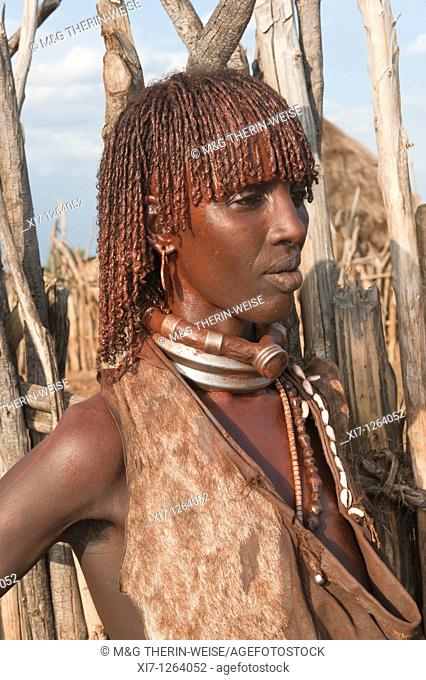 Young Hamar woman with red clay in her hair and wearing a goat dress, Omo river valley, Southern Ethiopia