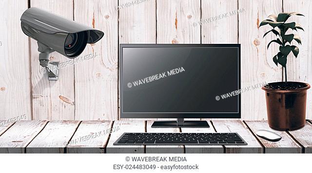 Composite image of a computer over a desk