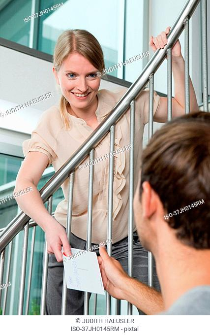 Woman handing postcard to boyfriend