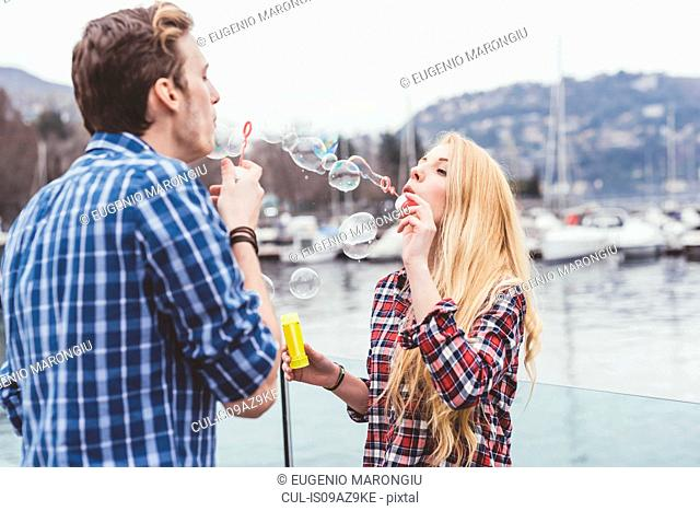 Young couple on waterfront blowing bubbles at each other, Lake Como, Italy