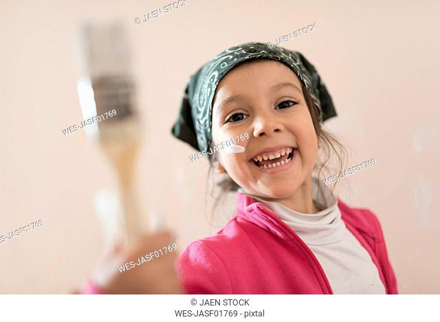 Portrait of happy little girl with paintbrush