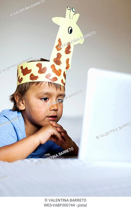 Little boywith self-made headdress lying on bed looking at laptop