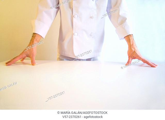 Cook behind a white table, hands on the table