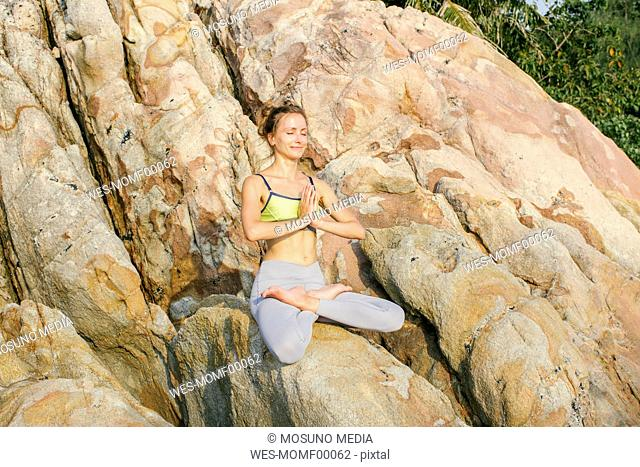 Woman sitting in lotus seat, meditating on the beach
