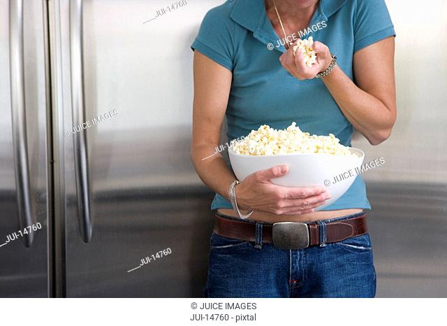 Woman with popcorn in kitchen, mid section
