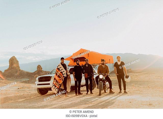 Motorcyclist friends beside off road vehicle, Trona Pinnacles, California, US