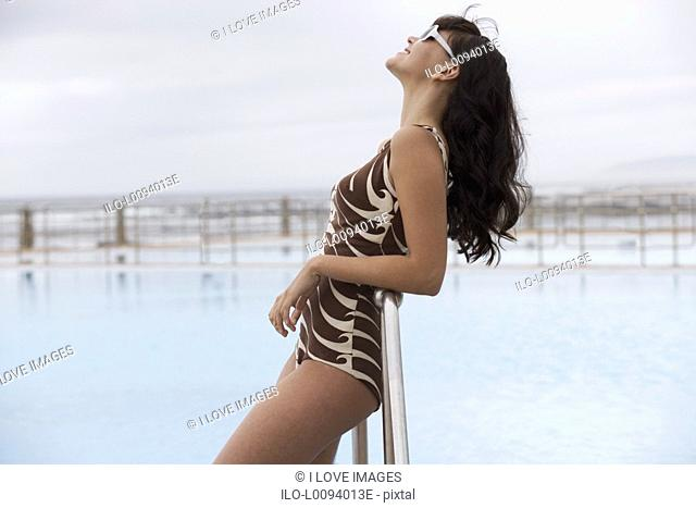 A young woman standing by a swimming pool