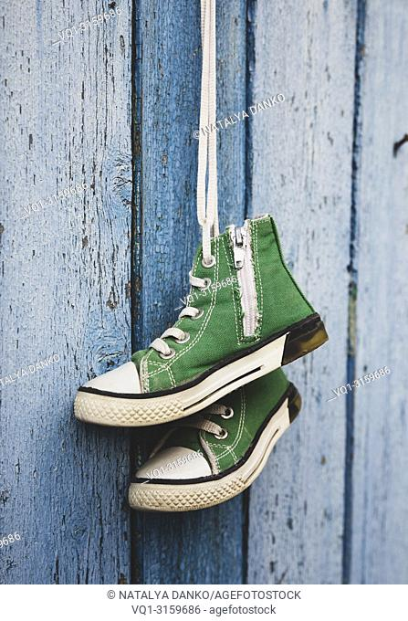 pairs of old textile children's green classic sneakers hang on a cord, blue shabby wooden background