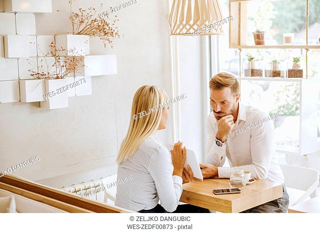 Businessman and businesswoman having a meeting in a cafe