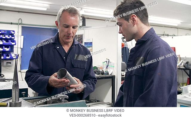 Engineer explaining to male apprentice how to operate factory machine.Shot on Sony FS700 in PAL format at a frame rate of 25fps