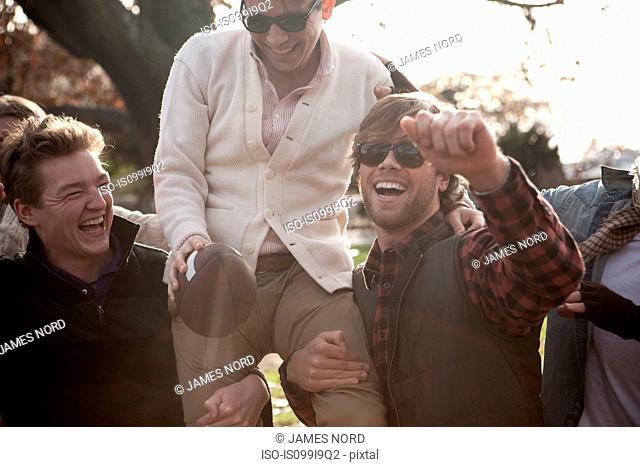 Friends carrying winner on shoulders