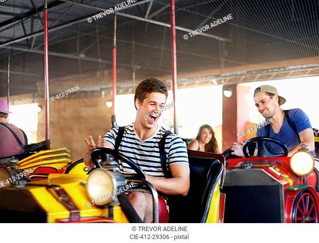 Laughing young men riding bumper cars at amusement park