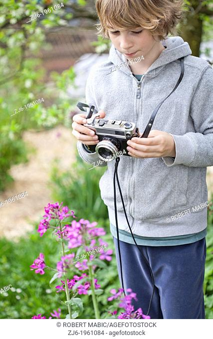 Boy photographing flowers in the garden