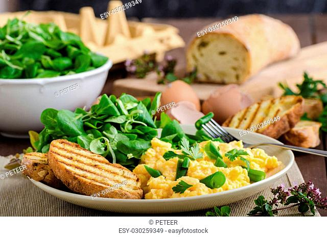 Scrambled eggs with beans and salad, baked baguette on a panini