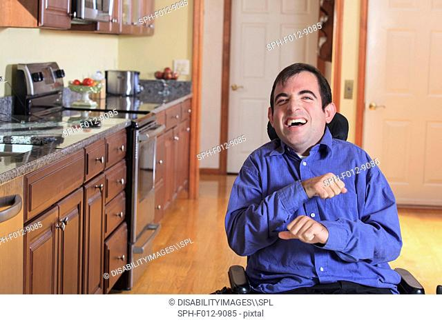 Man with Cerebral Palsy in his motorized wheelchair laughing while in his kitchen