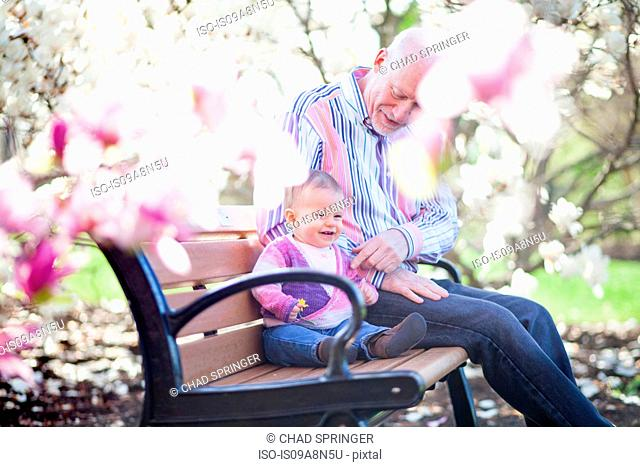 Grandfather and granddaughter together in park