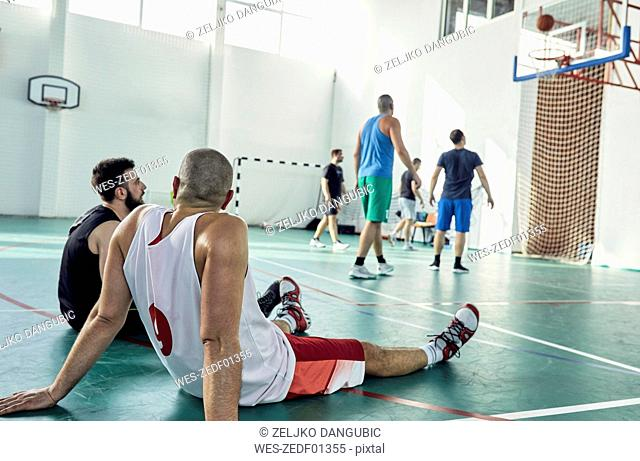 Basketball players during break, sitting on court