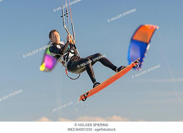 Germany, Baden-Wuerttemberg, Fischbach, Kitesurfer mid-air above Lake Constance