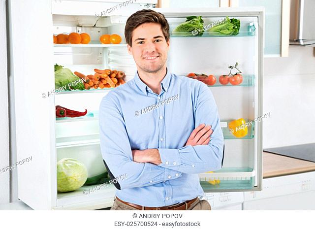 Portrait Of Handsome Man With Armcrossed Standing In Front Of Open Fridge