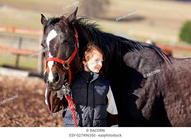 Happy and smiling girl with her horse holds the red reins and lead it through the paddock