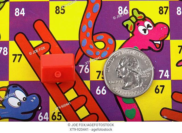 one us quarter dollar 25c coin and toy red house on a snakes and ladders board with house on the ladder and quarter on the snake