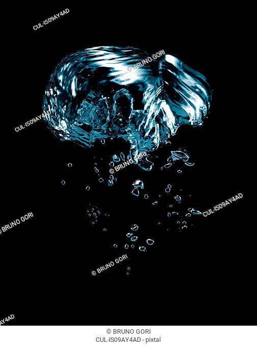Transparent liquid and bubbles rising against black background