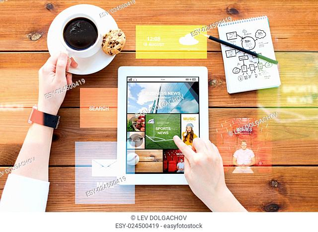 business, technology, media and people concept - close up of woman with internet news on tablet pc computer screen, notebook and coffee on wooden table