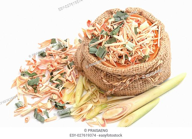 Sliced and dried lemongrass in clay pot on white background