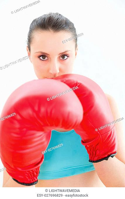 Close up portrait of a beautiful young woman in red boxing gloves against wall at fitness studio