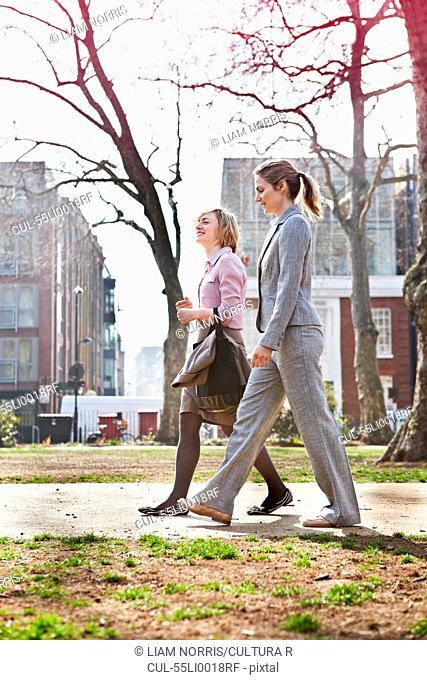 Two businesswomen walking on path in park