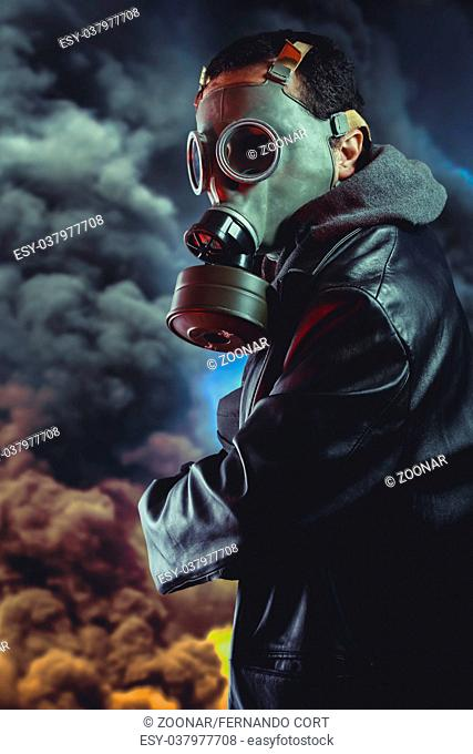 Armed man with gas mask over explosion background