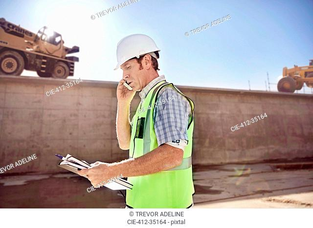 Construction worker foreman talking on cell phone at sunny construction site