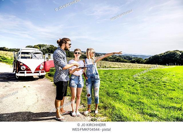 Friends with tablet outside van in rural landscape