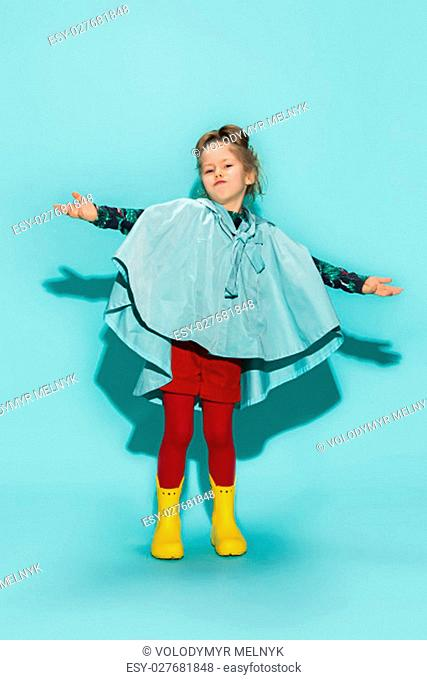 Little girl posing in fashion style wearing autumn clothing on blue background. Rubber yellow boots